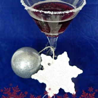 Sangria cocktail in a martini glass with Christmas ornaments