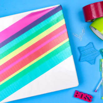 binder with colorful duct tape and school supplies on a blue background