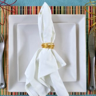 wrapped wire napkin ring holding white napkin on square white plates and a colorful placemat
