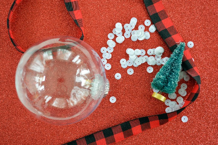 plastic ornament, sequins, ribbon and a mini tree on a red background
