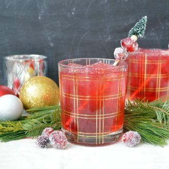 Cranberry cocktails with sugared cranberries next to ornaments and pine swags