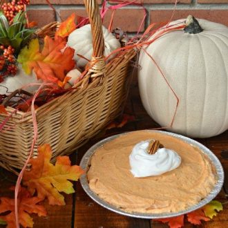 pumpkin cream pie next to a pumpkin and fall leaves