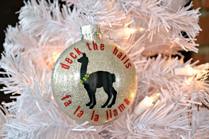 glitter ornament with fa la la llama vinyl design on a white tree