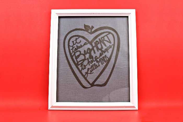paper cut teacher design in a white frame on a red background