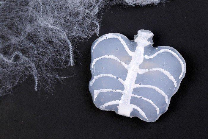 DIY glue gun skeleton jewelry on a black background