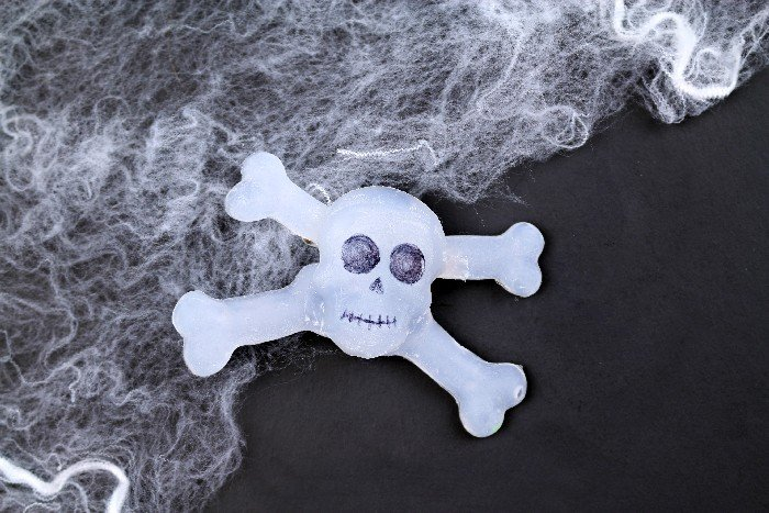 DIY glue gun skull and crossbones jewelry on a black background