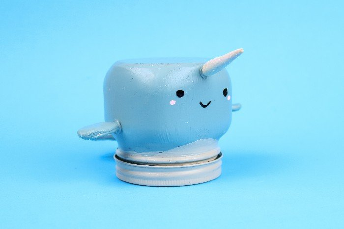 narwhal painted mason jar on a blue background
