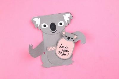 Cricut cut koala and baby card on a pink background