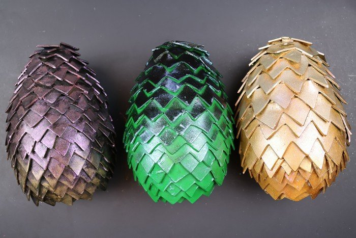 three diy dragon eggs on a black background