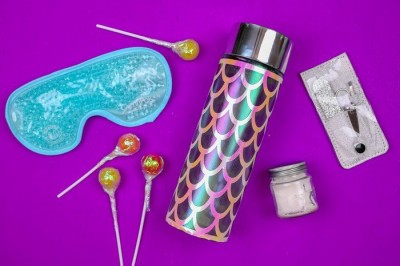 cricut vinyl on a water bottle with eye mask and manicure tools on a purple background