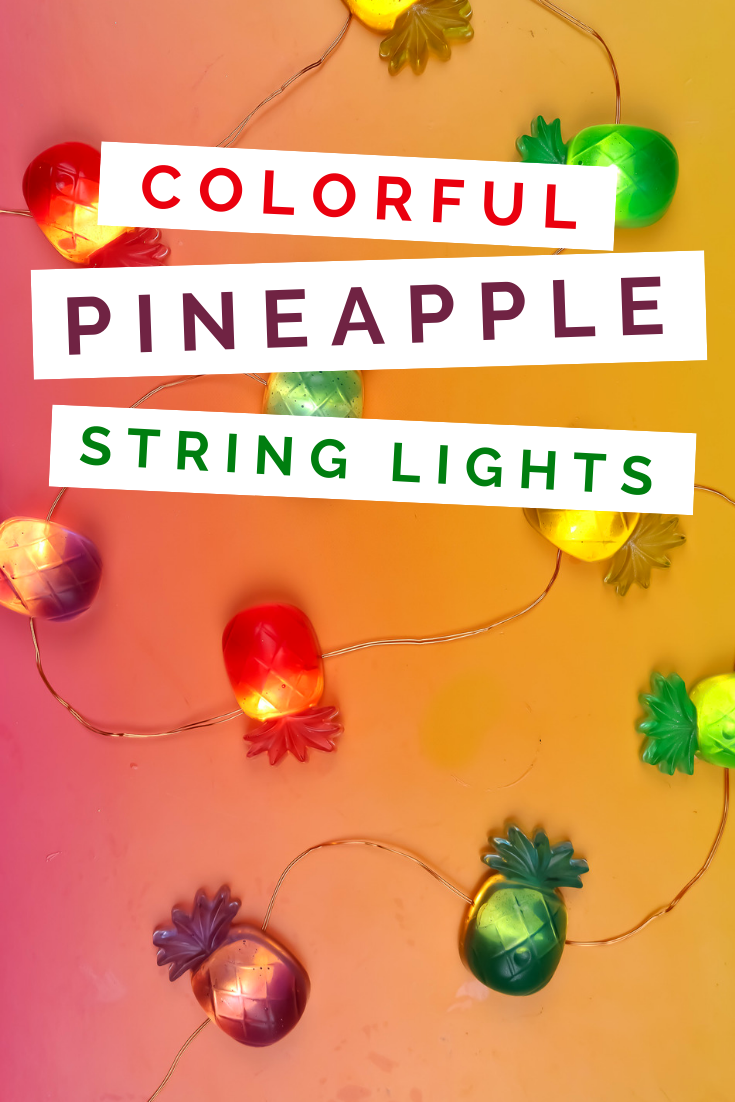 colorful resin pineapples on a string light on a pink and orange background