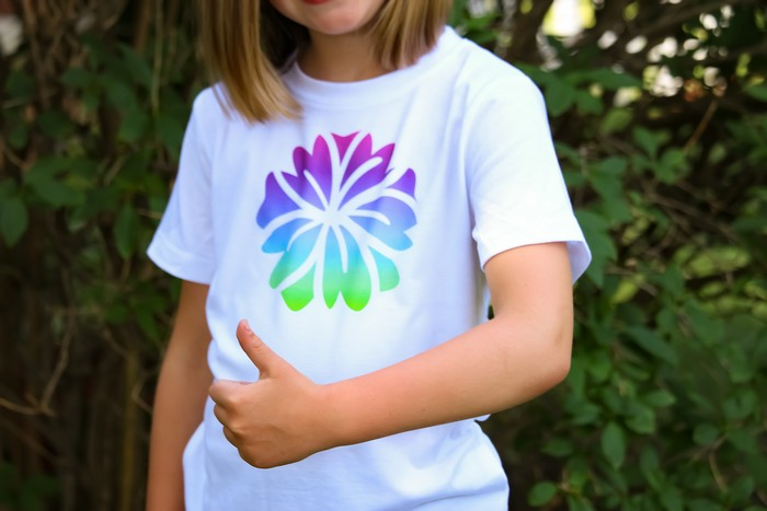 A little girl wearing an infusible ink shirt and giving a thumbs up