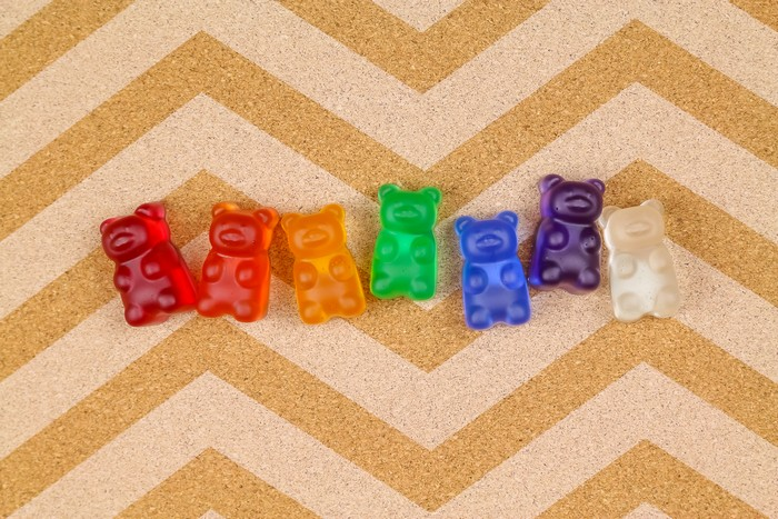 Rainbow resin gummy bear thumbtacks on a bulletin board