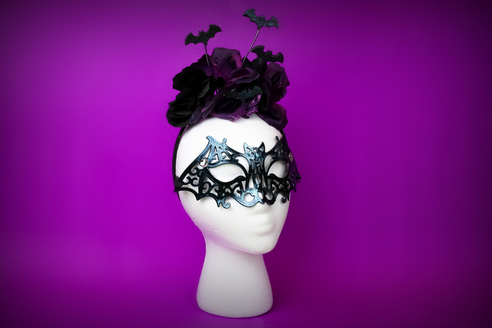 DIY halloween bat accessories on a foam head on a purple background