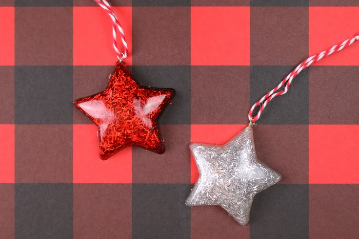 glittery star ornaments on a red buffalo check background