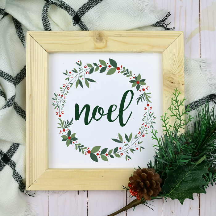Noel printable in a wood frame with pine branch and plaid scarf