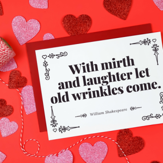 Shakespeare Valentine card with red envelope next to baker's twin and glitter hearts