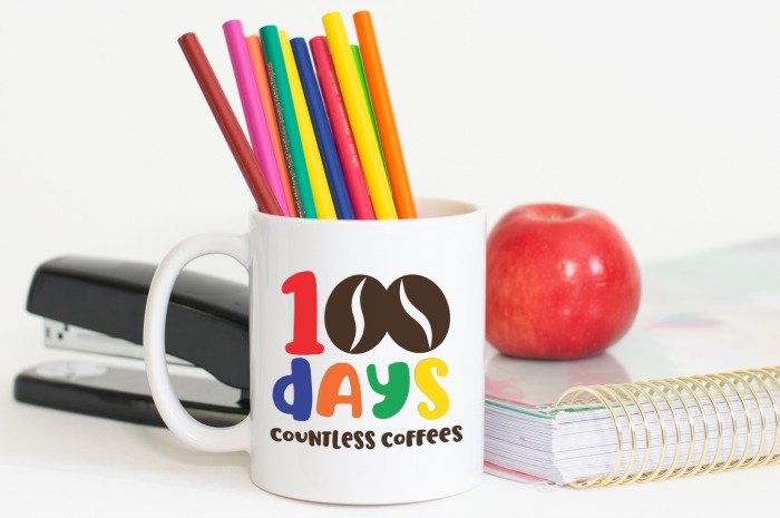 100 Days Countless Coffees SVG design on a white mug full of colored pencils, and apple and a stapler