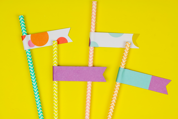 Cricut cut flags on paper straws on yellow background