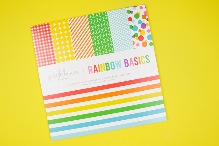 pack of rainbow scrapbook paper on a yellow background