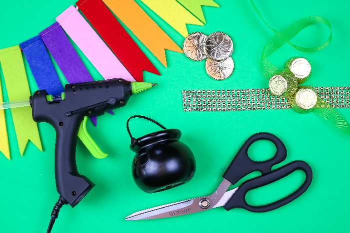 glue gun, mini pot, scissors, and gold craft supplies on green background with rainbow bunting