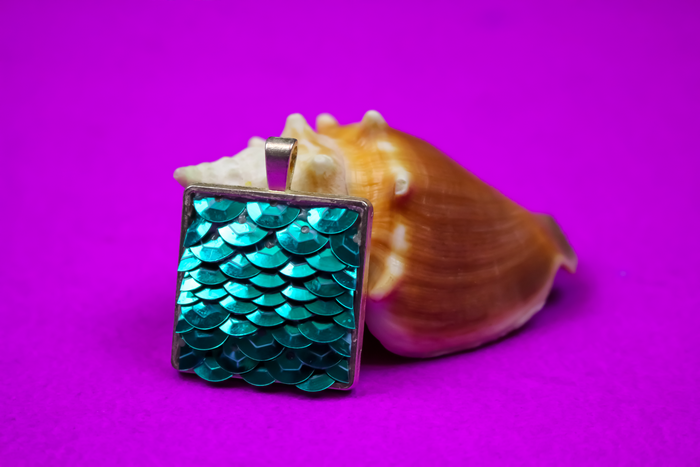 teal sequin mermaid pendant leaning on a seashell on a purple background