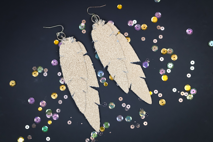 Cricut leather feather earrings on a black background with sequins
