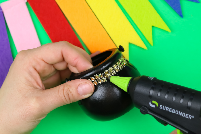 hands gluing rhinestone ribbon to fit a mini pot of gold with a glue gun