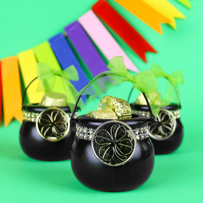 3 St. Patricks Day favors on a green background with rainbow bunting