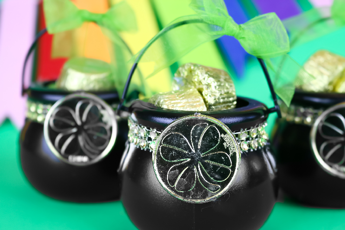 close up of mini pots of gold on a green background with rainbow bunting