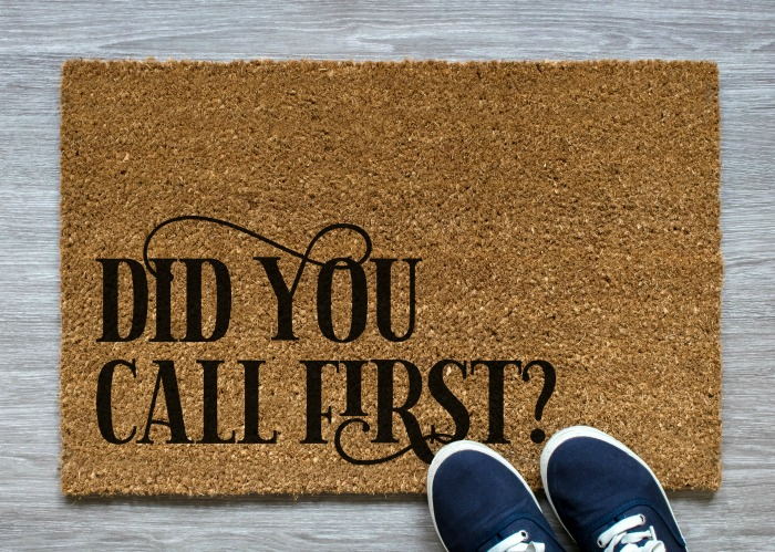 Coir door mat that reads Did You Call First next to navy sneakers