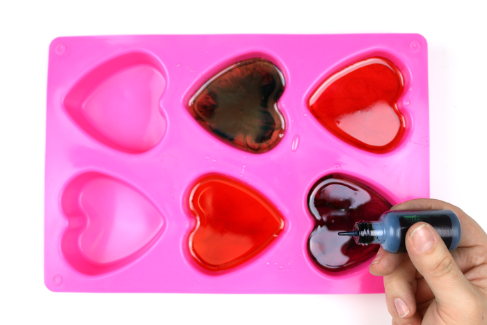 silicone heart mold filled with resin that has been colored with alcohol ink