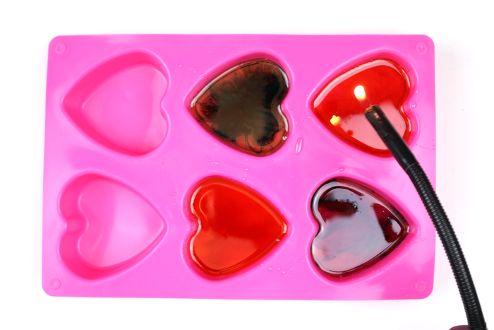 candle lighter over silicone heart mold filled with resin