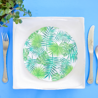 Glass plates decoupaged with tropical paper on a white plate next to a plant