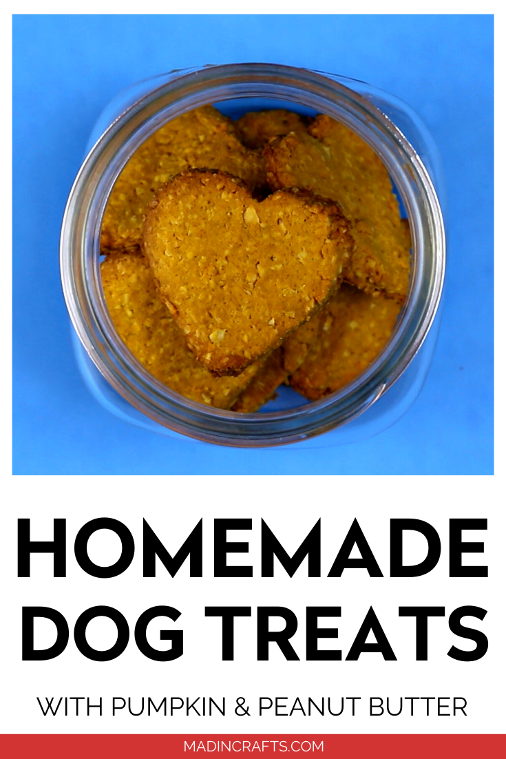 Mason jar with heart shaped homemade dog treats on blue background