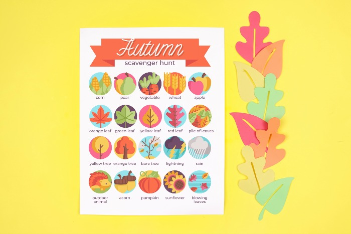 Autumn Scavenger hunt printable with colorful paper leaves on a yellow background